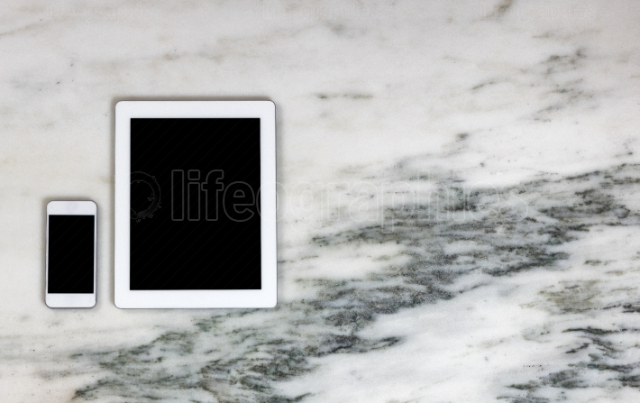 Modern mobile communication devices on marble desktop