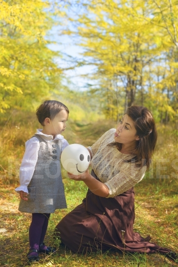 Mother and daughter in forest with balloon in autumn
