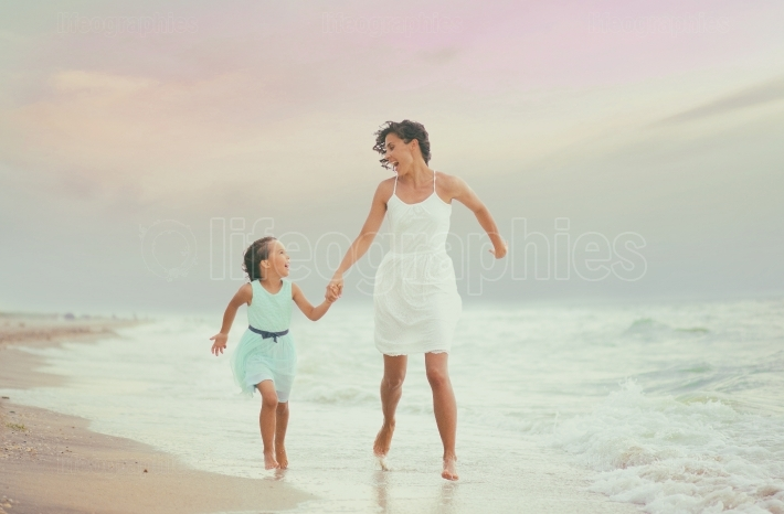 Mother and her daughter runing and having fun on the beach
