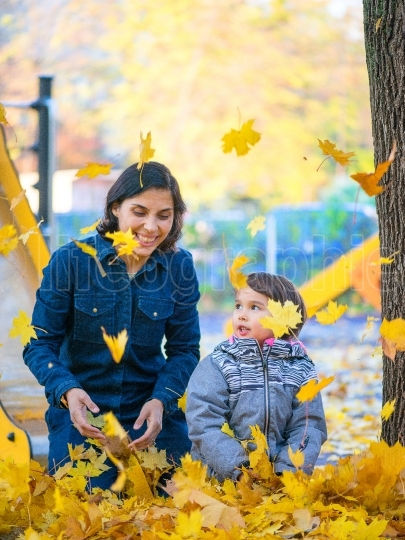 Mother and her little daugheter having fun in park with leaves