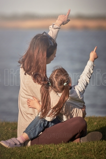 Mother and little girl enjoying time together pointing with finger to the sky