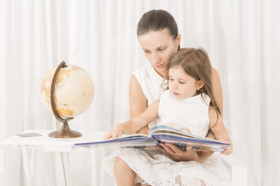 Mother reading a book to her little daughter at home