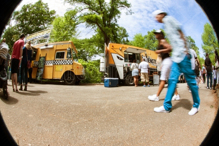 Motion blur fisheye perspective of people walking by food trucks