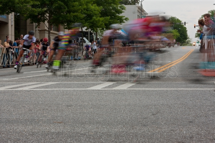Motion blur of male cyclists turning corner in amateur race