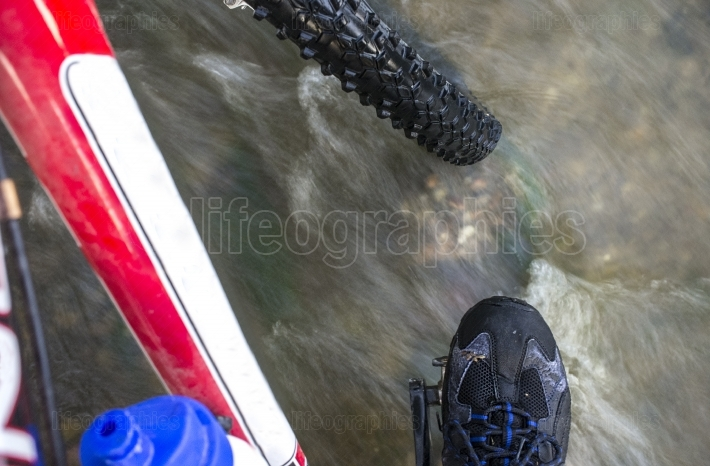 MTB biker crossing a shallow river pass
