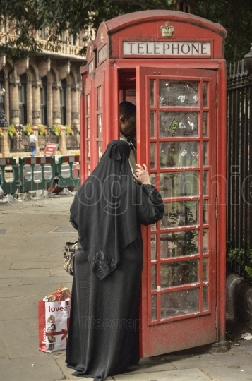 Muslim woman waiting at a red phone box in London