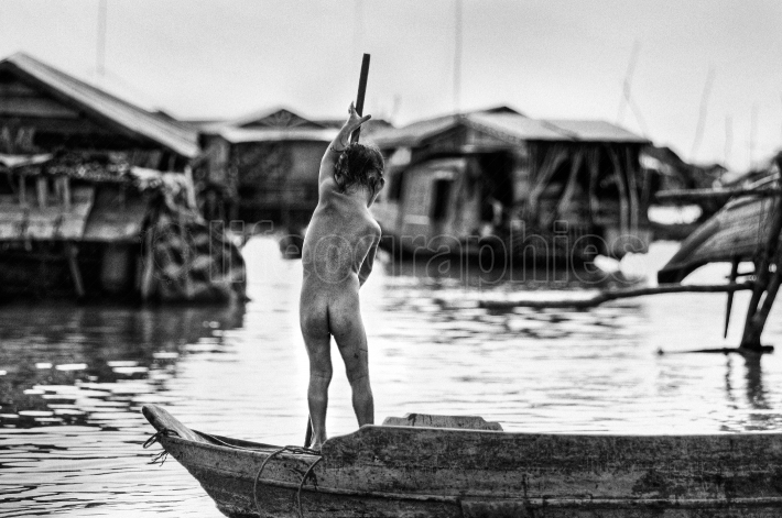 Naked kid rowing a boat on tonle sap, cambodia