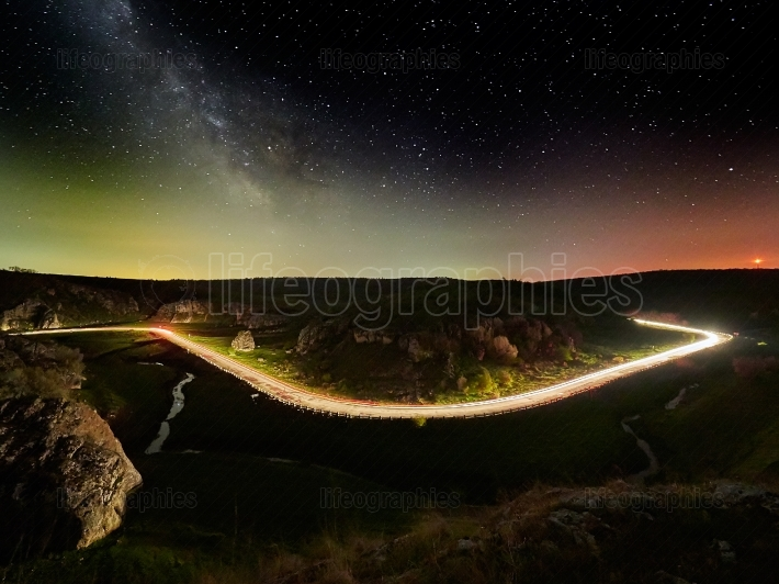 Night sky with milky way and stars, night road illuminated by ca