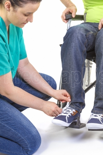 Nurse helping a disabled young man in wheelchair