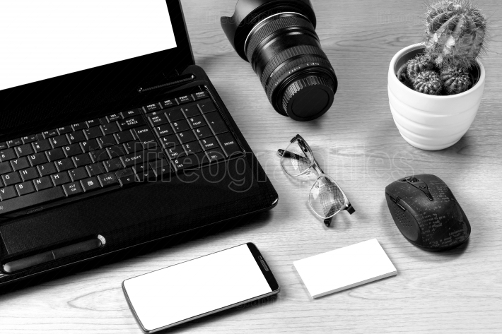 Office table with laptop computer, camera lens, smartphone, eyeg
