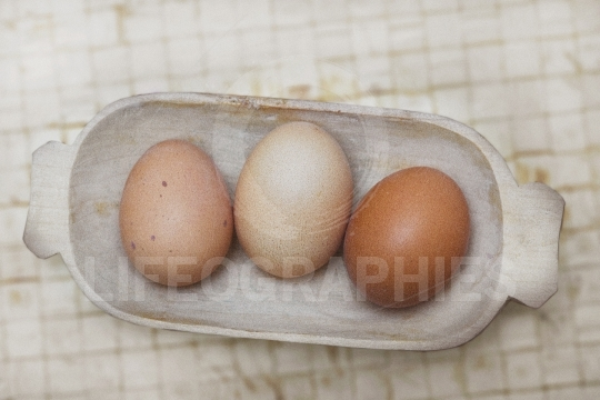 Old basket with three organic eggs.
