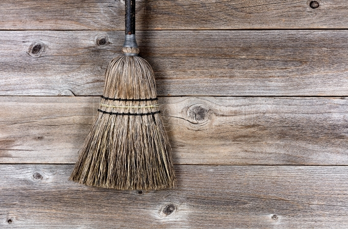 Old broom laying on rustic wooden boards