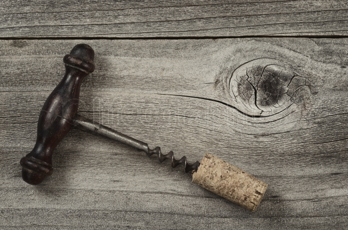 Old Corkscrew with attached cork on rustic wood