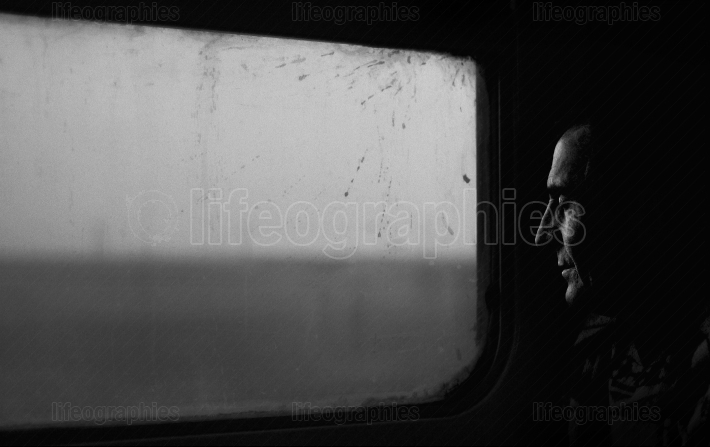 Old man meditating with closed eyes in front of a dirty train window