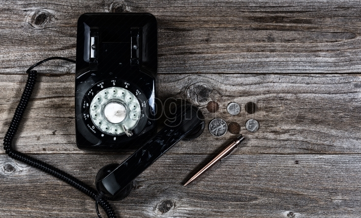 Old telephone with various old vintage objects on stressed wood