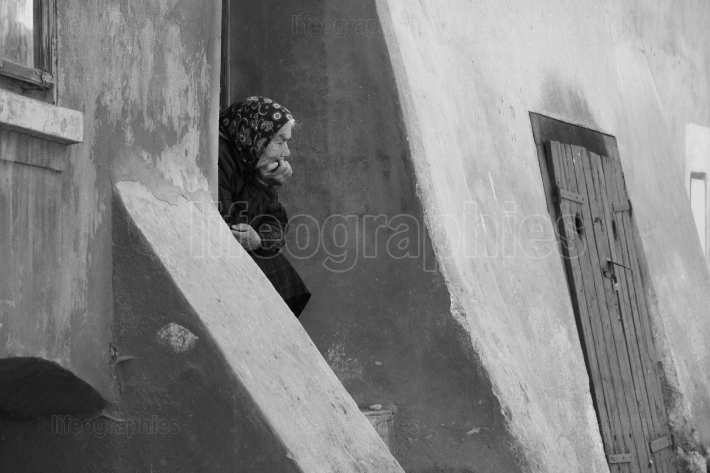 Old woman sitting in front of her house door