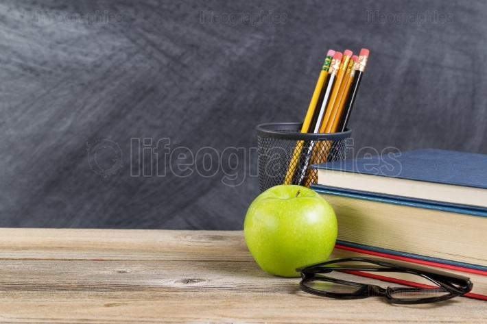 Old wooden desktop with green apple and reading materials