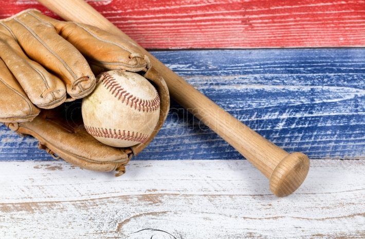 Old worn baseball equipment on faded boards painted in American