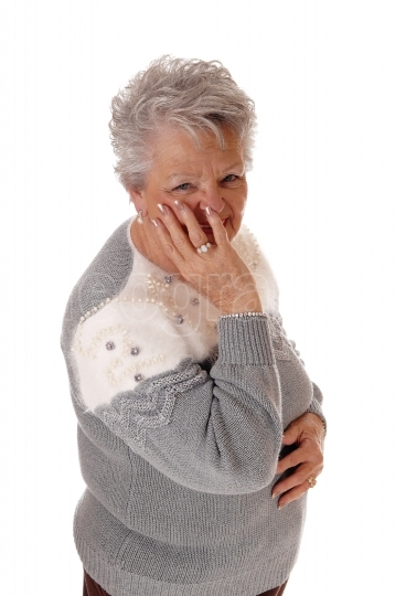 Older senior woman holding hand on face.