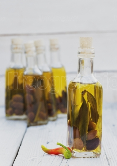 Olives and olive oil in mini bottle on wood table