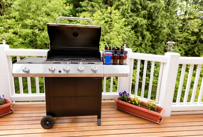 Open barbecue cooker and bottled beer on cedar wood outdoor deck
