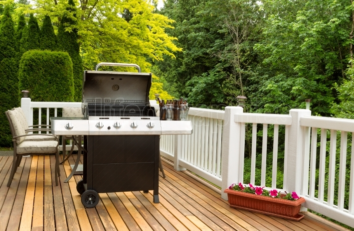 Open BBQ cooker and bottled beer on outdoor cedar patio