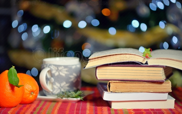 Open book, cup of hot drink and orange fruits