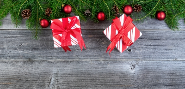 Overhead view of real Christmas fir tree branches and gifts on w
