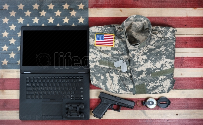 Overhead view of USA military equipment and laptop computer on r