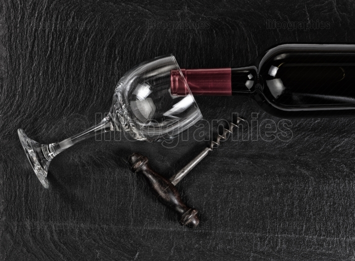 Overhead view of vintage corkscrew with red wine bottle and drin