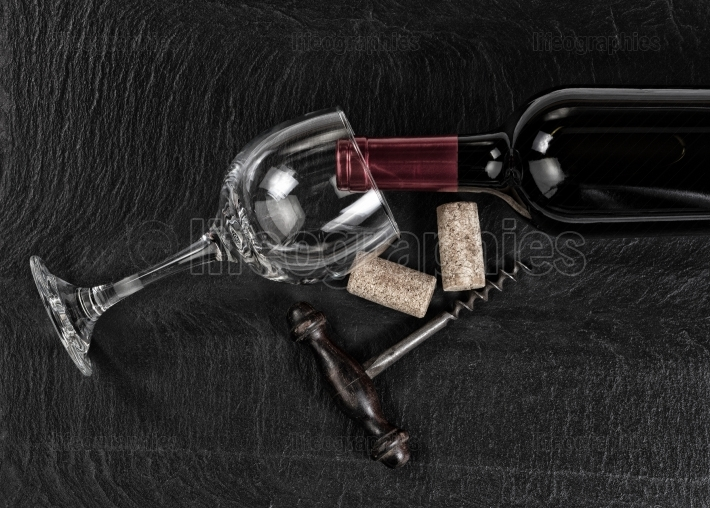 Overhead view of vintage corkscrew with red wine bottle and glas