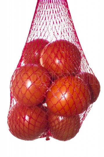 Packaged tomatoes hanging in red plastic net