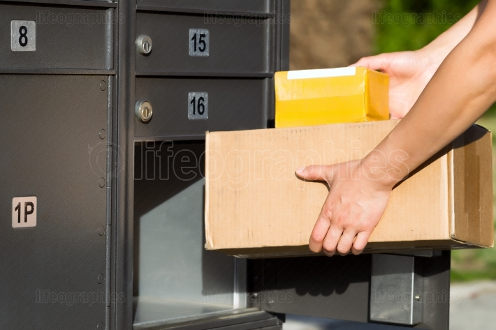 Packages being loaded into postal mailbox