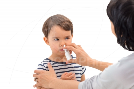 Parent of a girl applies a nasal spray