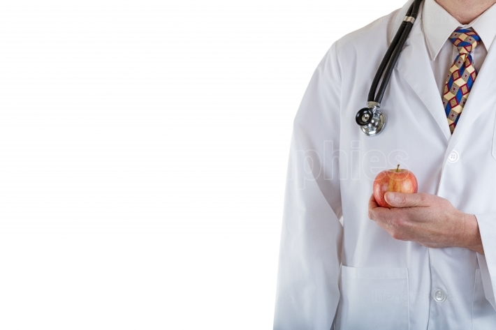 Partial front view of doctor holding apple on white background