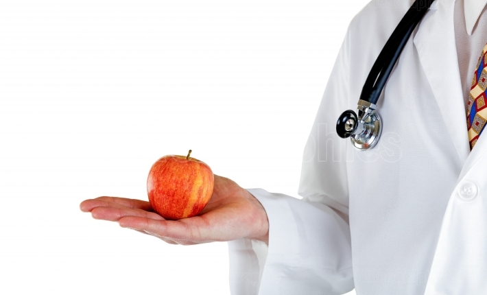 Partial side view of doctor holding apple on white background
