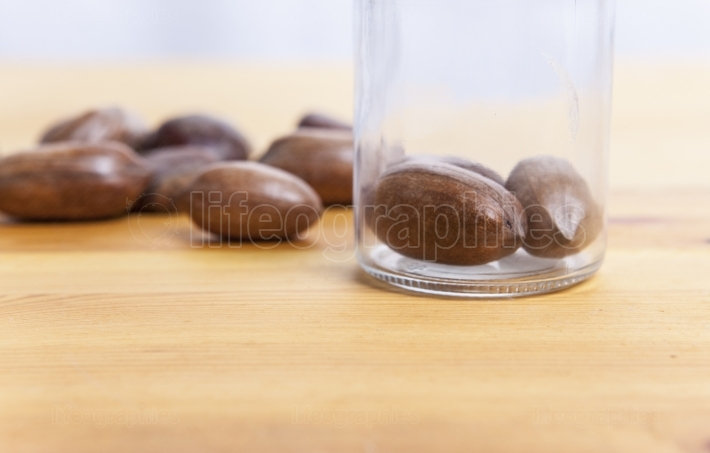 Pecan walnuts on glass jar over wooden surface