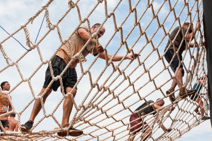 People climb cargo net at extreme obstacle course race