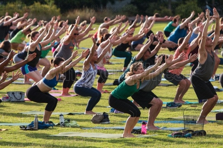 People Do Utkatasana Pose In Outdoor Group Yoga Class