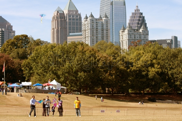 People Fly Kites In Park Against Atlanta City Skyline