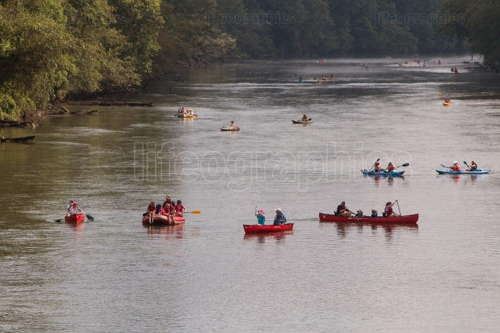 People Raft And Canoe Down River On Hot Summer Day
