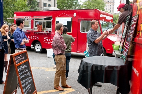 People stand in line to order meals from food truck