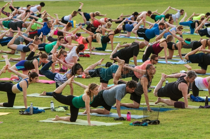 People Stretch Right Leg In Unison At Outdoor Yoga Class