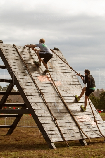 People Use Ropes To Climb Wall In Extreme Obstacle Race
