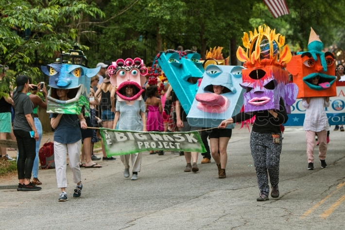 People Walk In Parade Wearing Huge Creative Masks On Heads