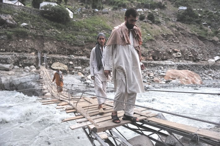 People walking on a bridge across the mudslide that has blocked access on the road from gilgit to skardu