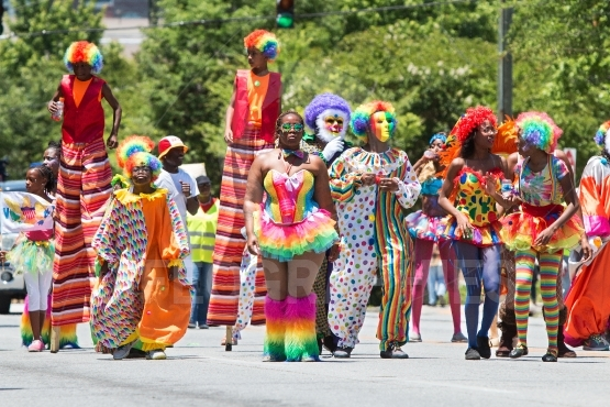 People wearing clown costumes walk in caribbean culture parade