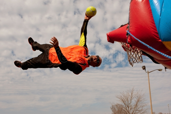 Performer gets sideways in midair attempting to dunk ball