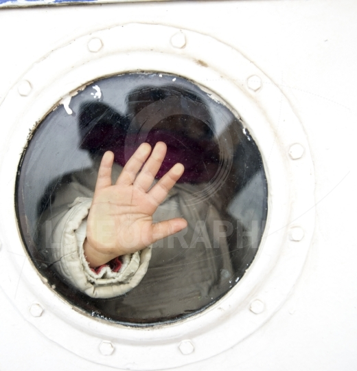 Photo of child hand on a ship vindow