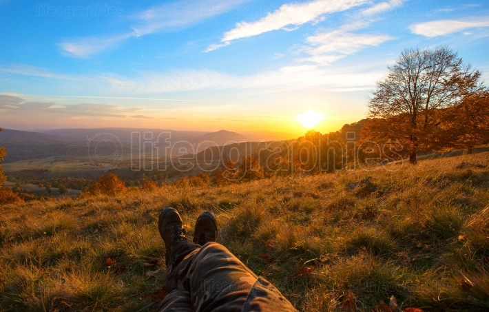 Photographer resting and having beautiful view of mountains at sunset